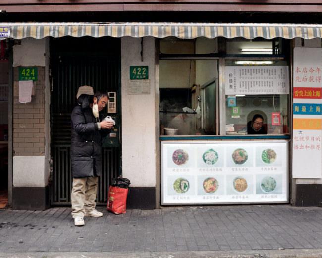 Ein Mann steht vor einem Gebäude, aus dem Essen verkauft wird und hat seinen Mundschutz abgenommen, um sein Essen zu verzehren.