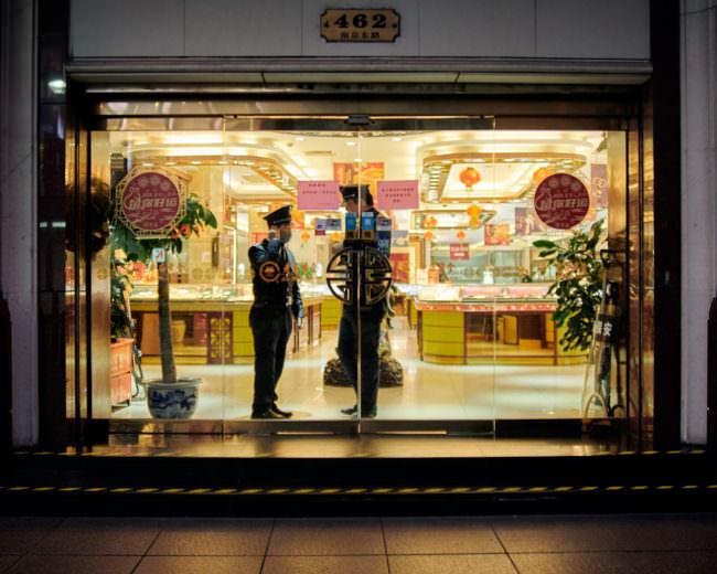 Zwei Polizisten mit Mundschutz stehen hinter den Glastüren eines Ladens