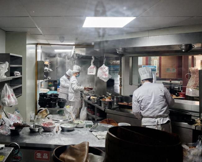 Köche verrichten ihre Arbeit mit Mundschutz