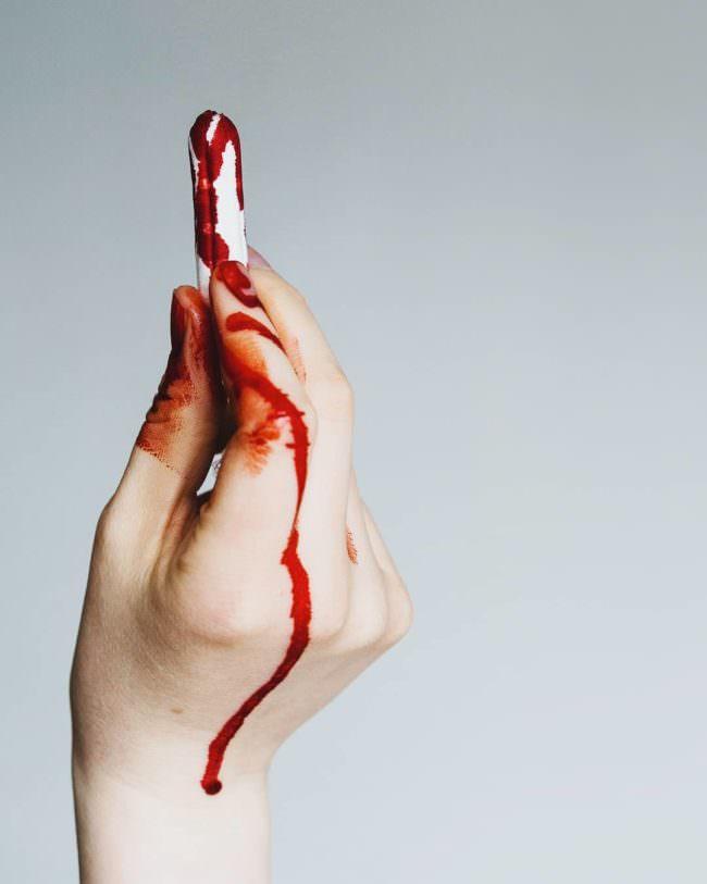 Blutiger Tampon wird nach oben gehalten
