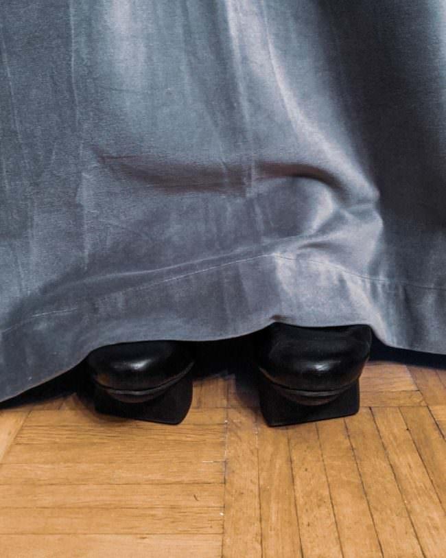 Schuhe hinter einem Vorhang