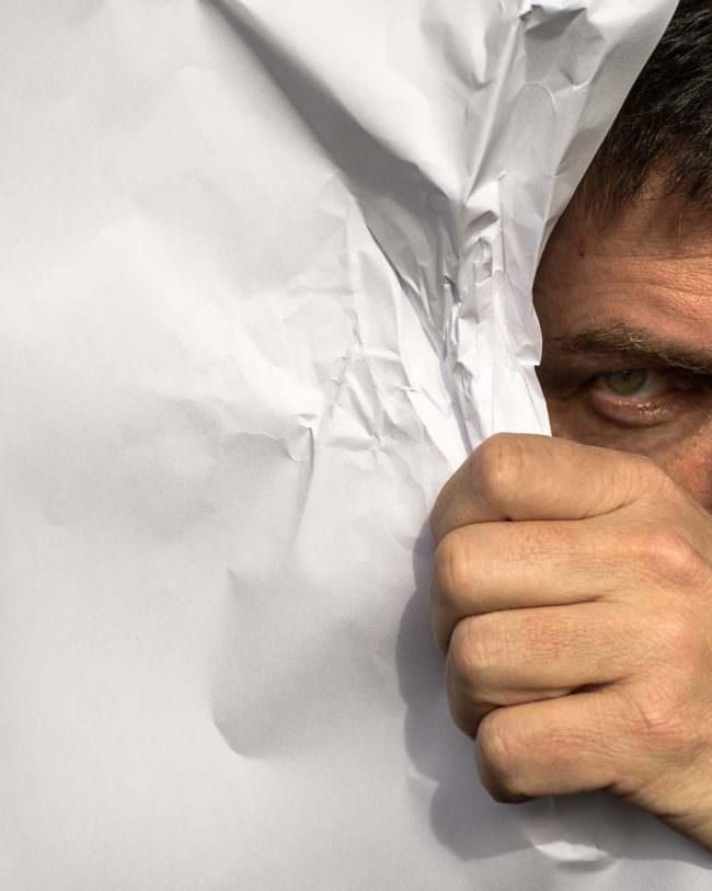 Mann versteckt sich hinter Papier