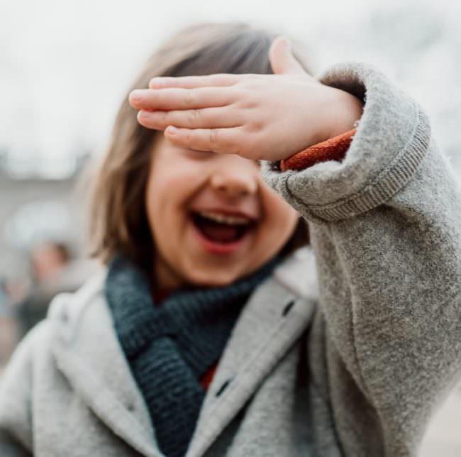 Kind hält lachend den Arm vor das Gesicht