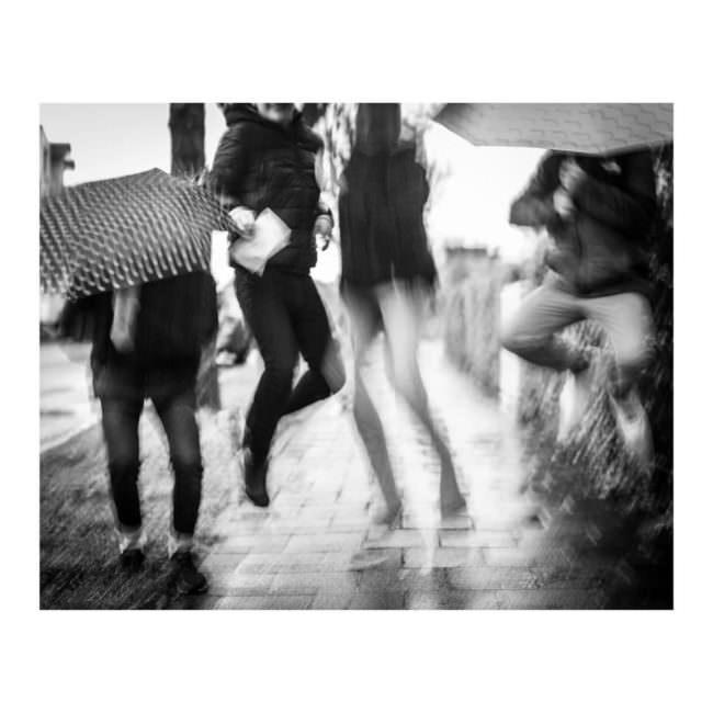 Menschen mit Regenschirmen springen