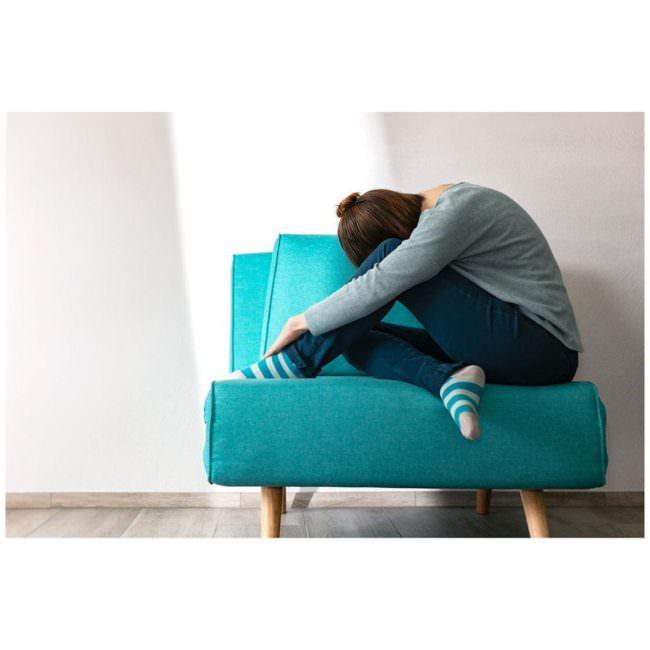 Frau gebeugt auf einem Sessel