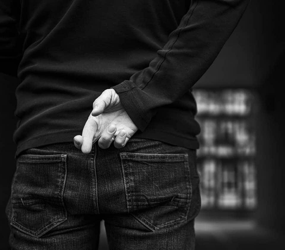Person kreuzt Finger hinter dem Rücken