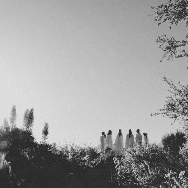 Personen stehen im Kreis in der Landschaft