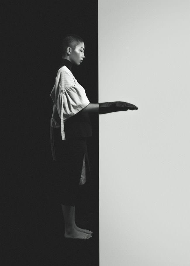 Person vor hell-dunkel-geteilter Wand