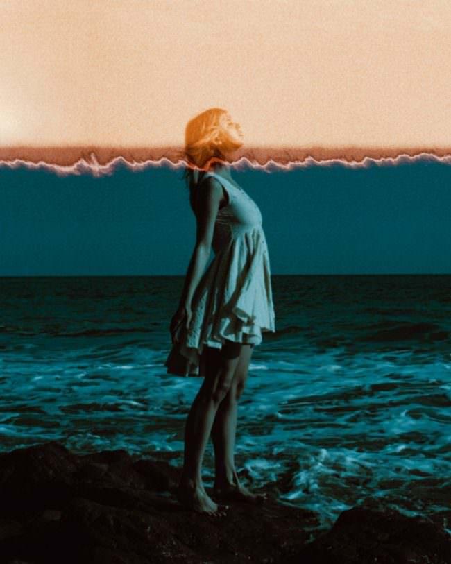 Frau steht vor Meer