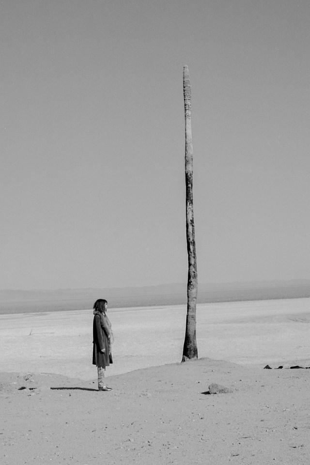 Person vor einer Säule in der Wüste