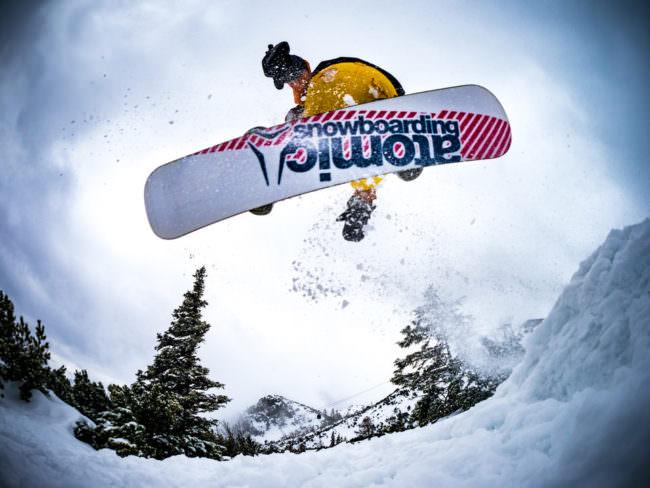 Person springt mit Snowboard