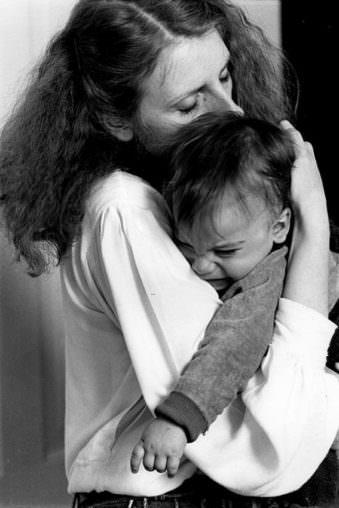 Frau hält ein Kind im Arm