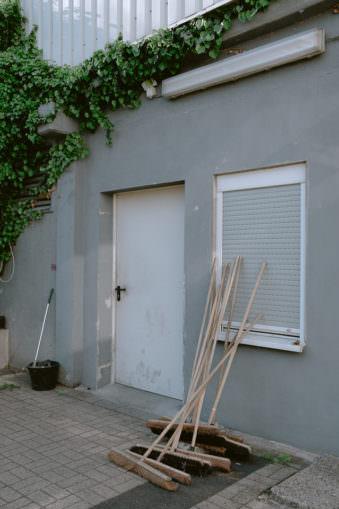 mehrere Besen lehnen an einer Wand
