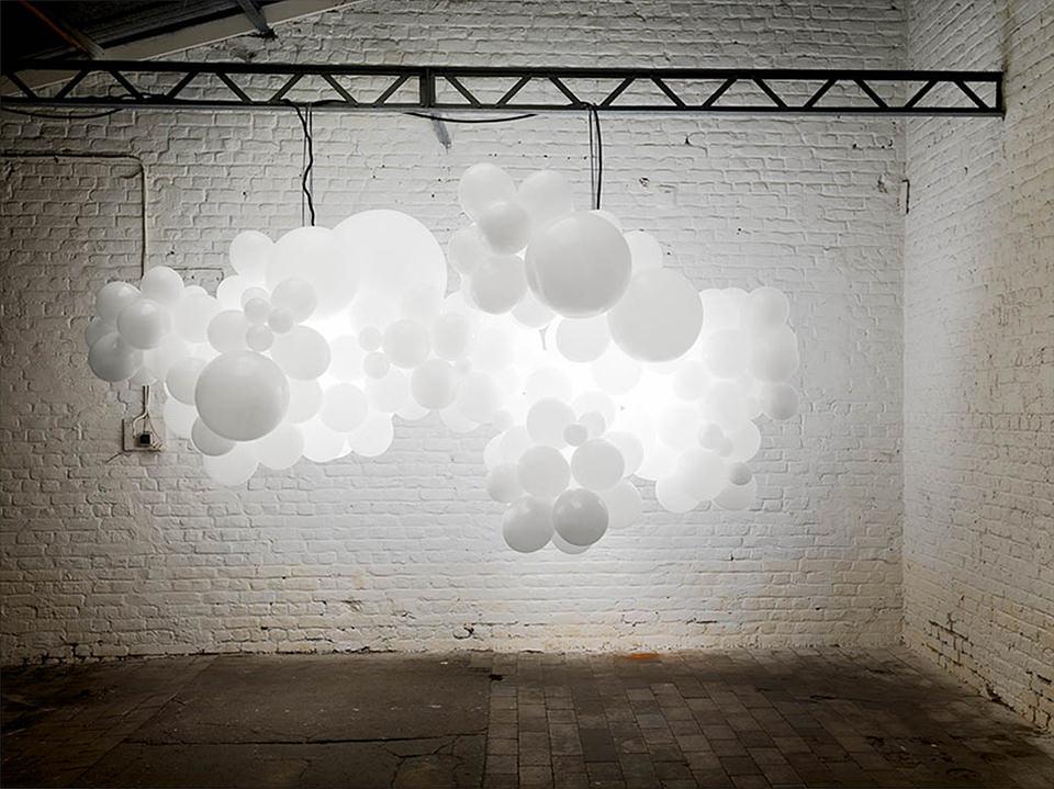weiße Ballons schweben als Wolke in einem Raum