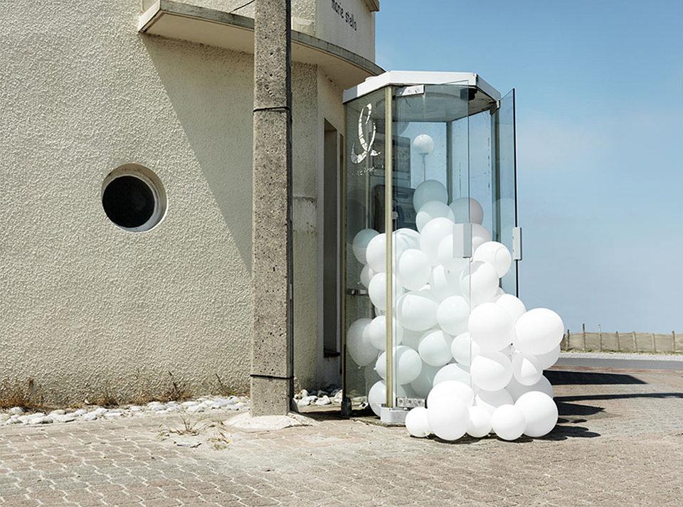 weiße Ballons in einer Telefonzelle