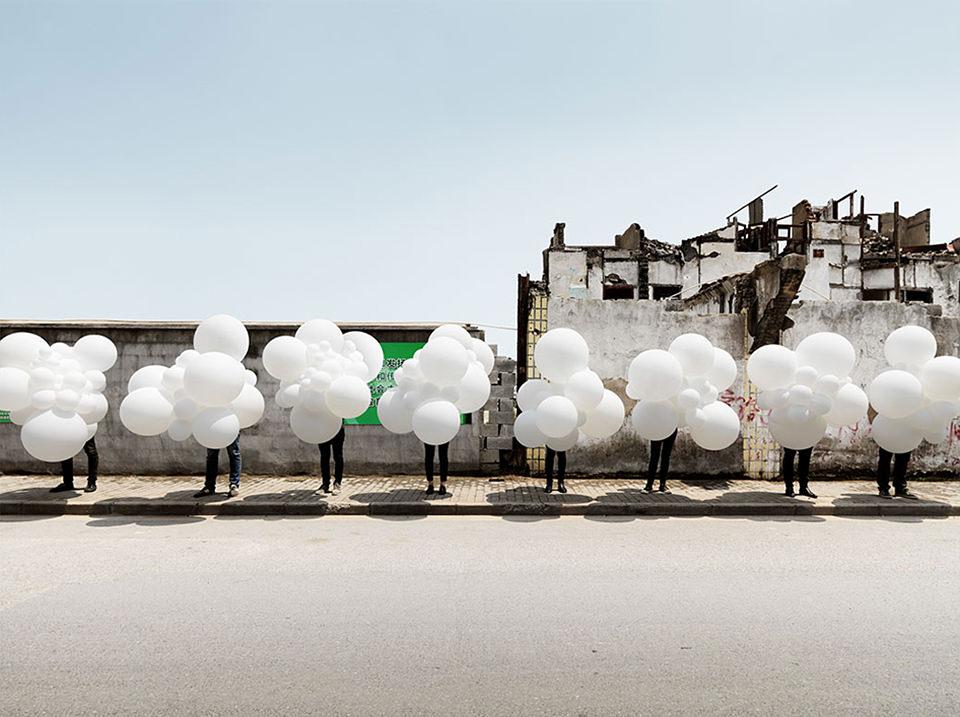 eine Reihe Menschen mit weißen Ballons
