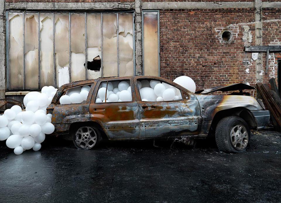 weiße Ballons in einem ausgebrannten Auto