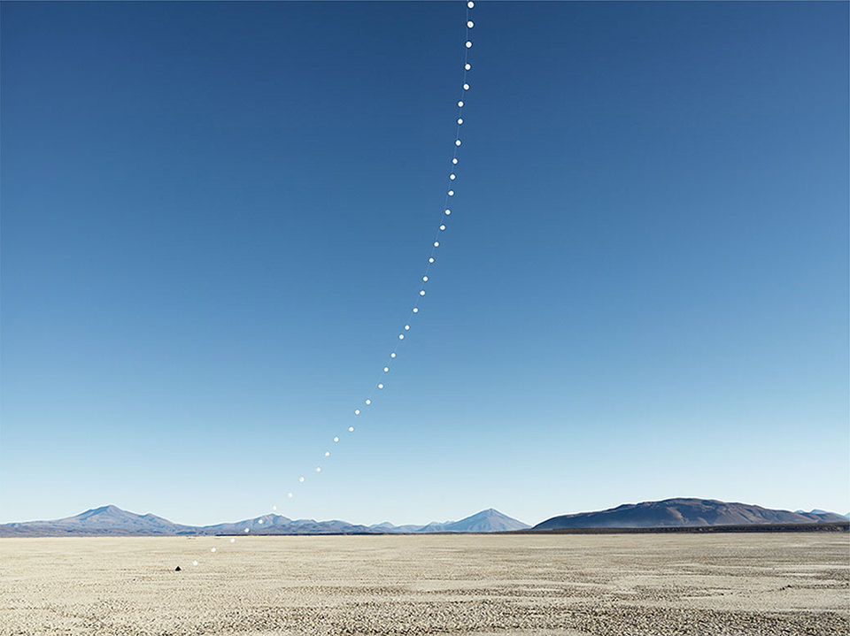 eine Kette weißer Ballons über einer Wüste