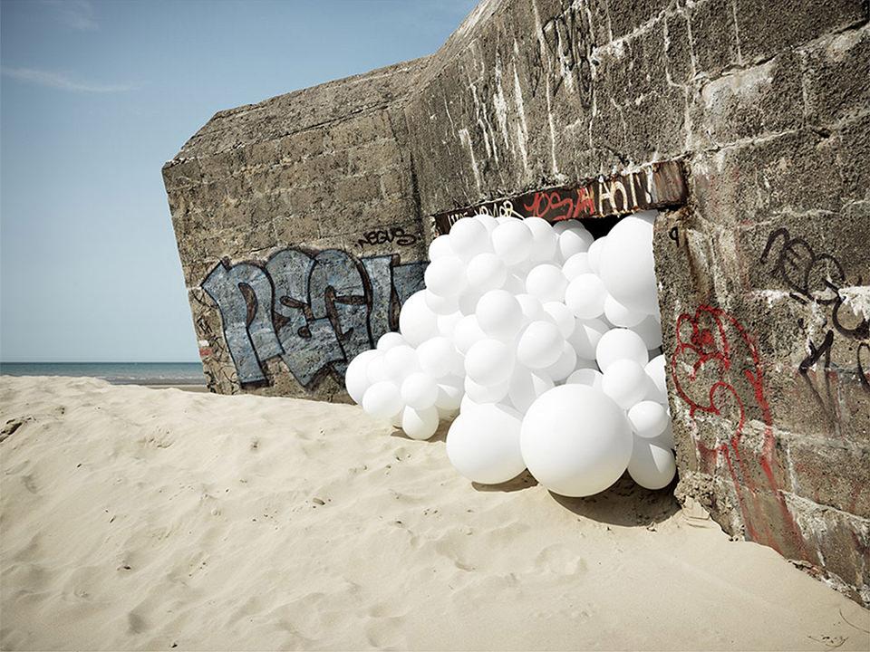 weiße Ballons quellen aus einem Bunker am Strand