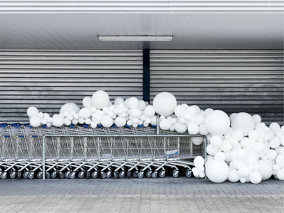 weiße Ballons auf einer Reihe Einkaufswagen
