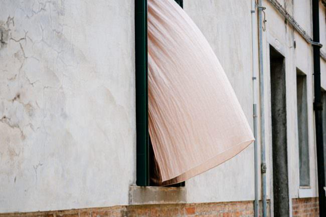Vorhang weht aus einem Fenster