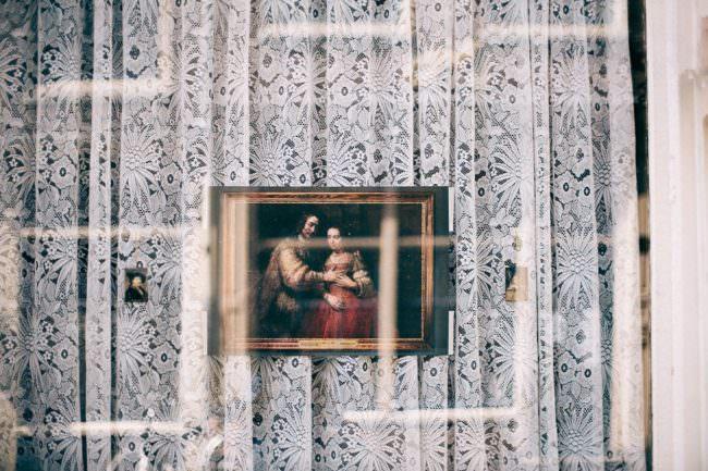 Heiligenbild vor Gardine mit Reflexionen