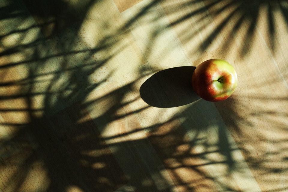 Apfel mit Schatten auf dem Tisch