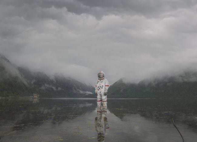 Astronaut steht im Wasser vor Bergen