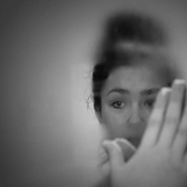 Frau sieht in einen beschlagenen Spiegel