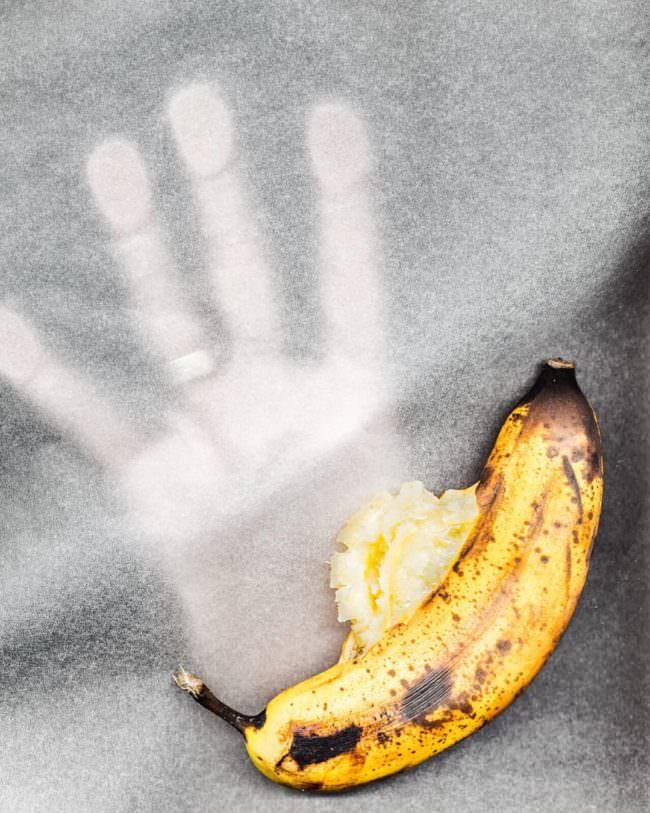 Hand zerquetscht eine Banane