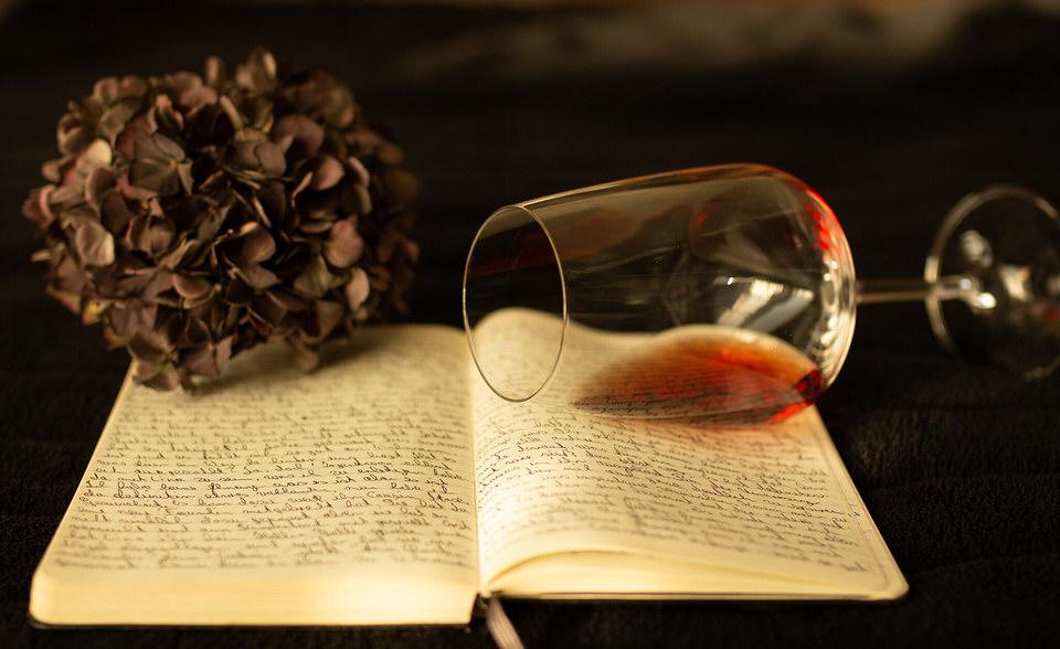 beschriebenes Buch auf dem ein Glas Wein liegt