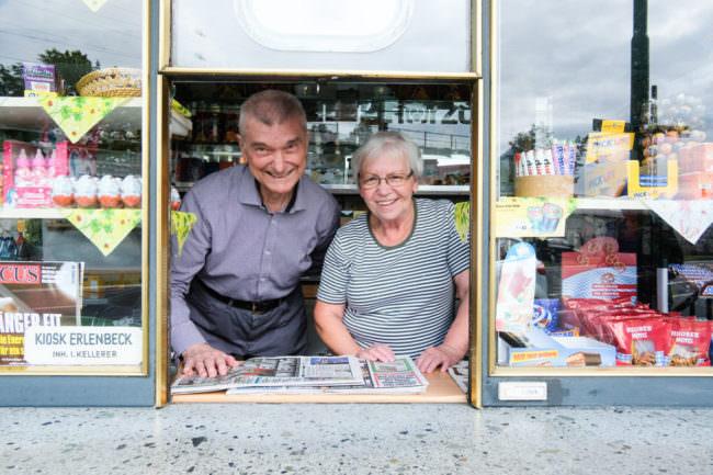 Zwei Menschen schauen aus einem Kioskfenster