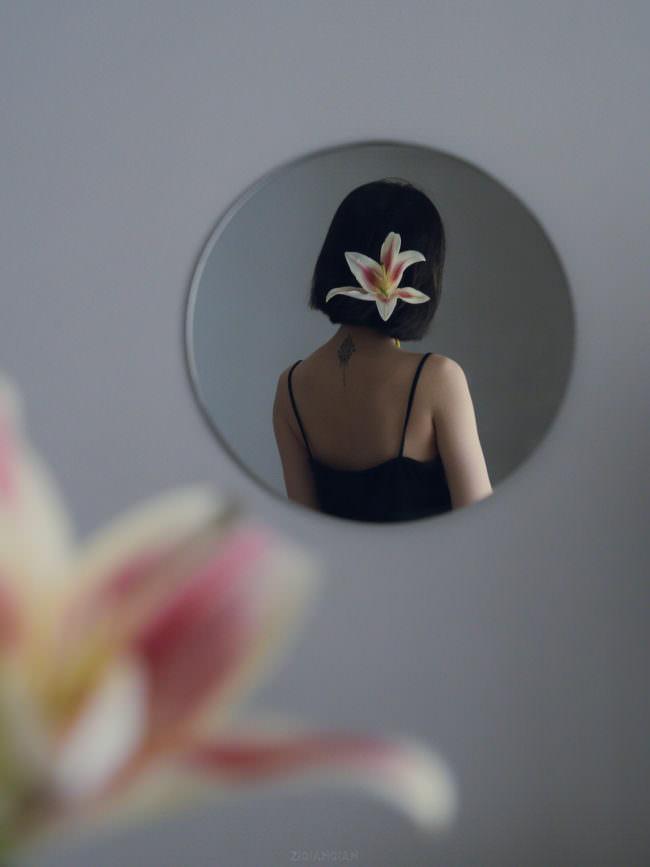 Person mit Orchidee im Spiegel