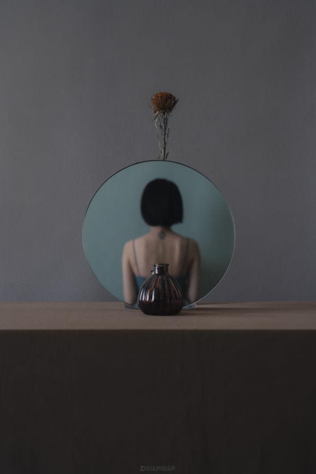 Person spiegelt sich im Spiegel. Davor steht eine Vase