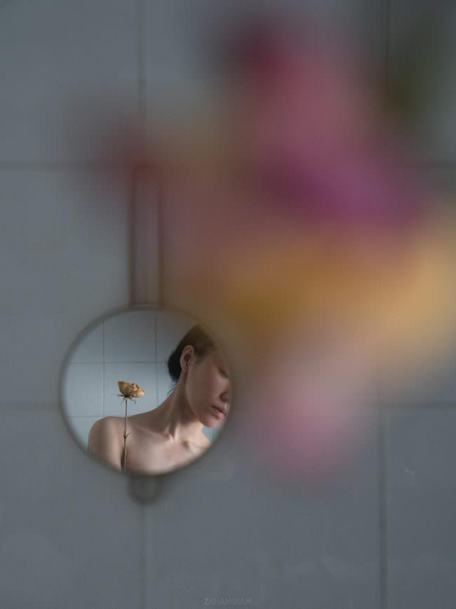 Person mit Blume im Spiegel