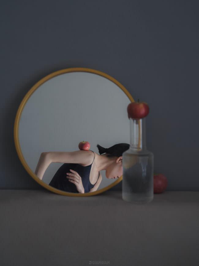 Frau balanciert eine Tulpe im Spiegel