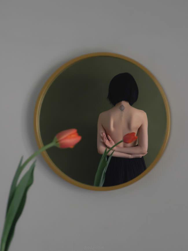 Frau mit Tulpe im Spiegel