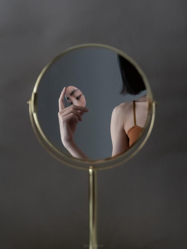 Eine Hand hält ein Gesicht im Spiegel