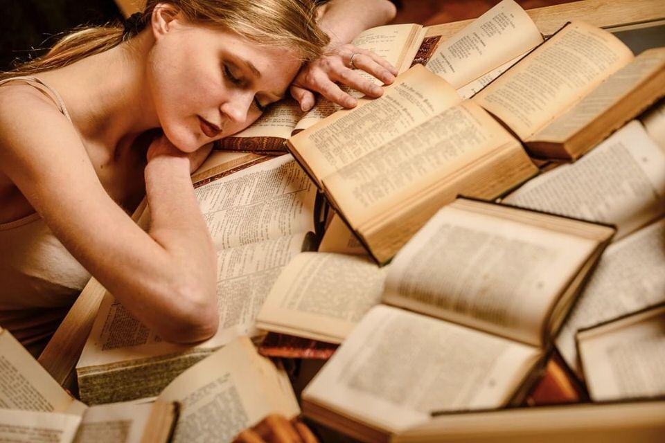 Frau liegt auf aufgeschlagenen Büchern