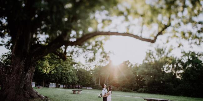 Ein Paar steht unter einem Baum, der in der Unschärfe verschwindet.