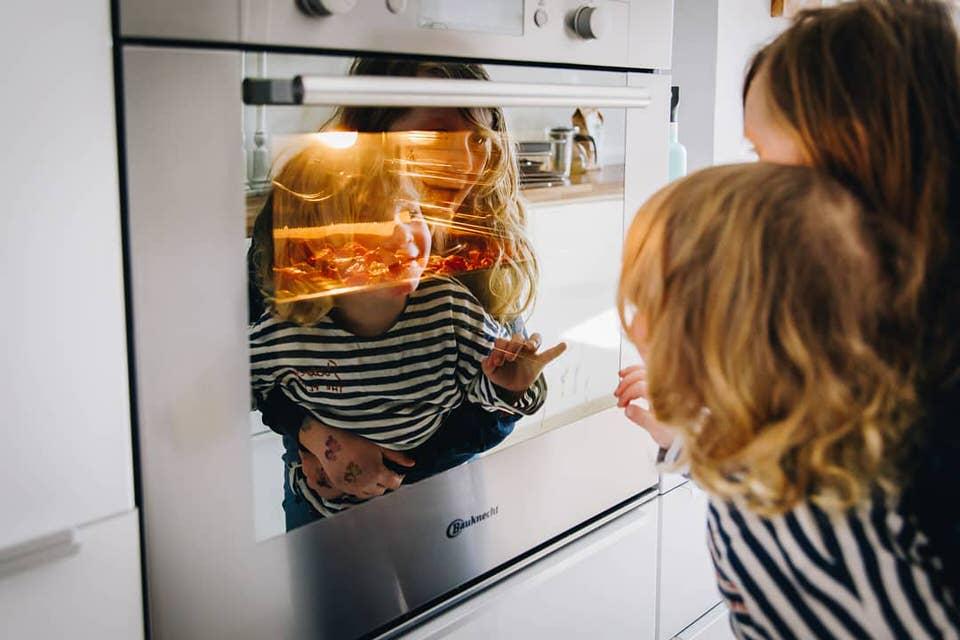 Eine Frau und ein Kind sehen in einen Ofen