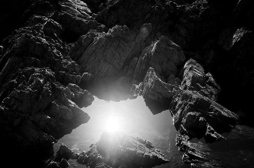 Licht bricht sich in einer Pfütze zwischen Steinen
