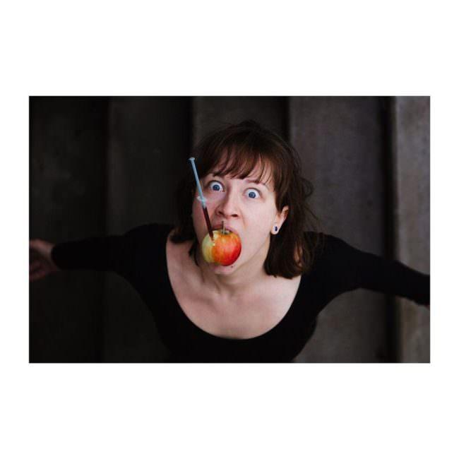 Frau mit Apfel im Mund in dem eine Spritze steckt