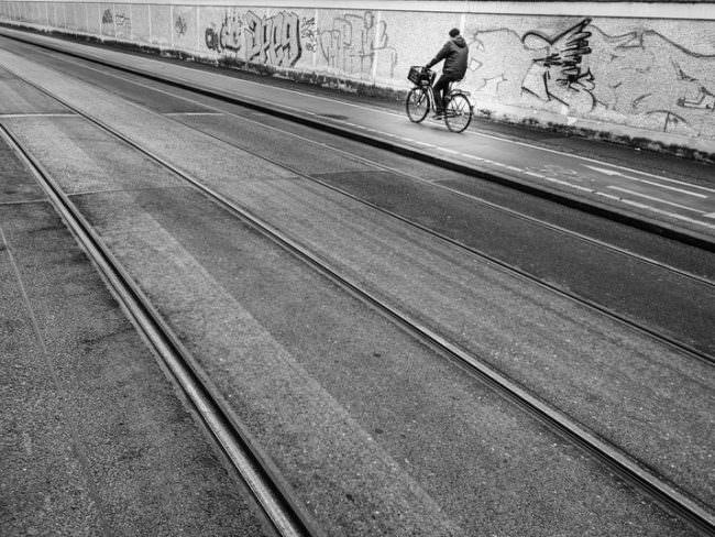 Radfahrer auf einer Straße mit Gleisen