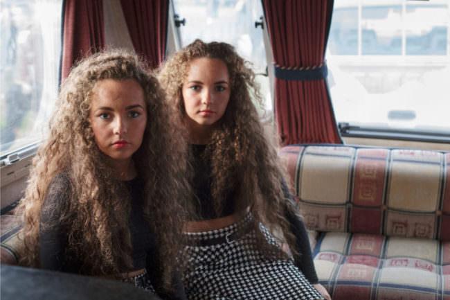 Zwei junge Frauen sitzen auf einem Sofa und sehen in die Kamera