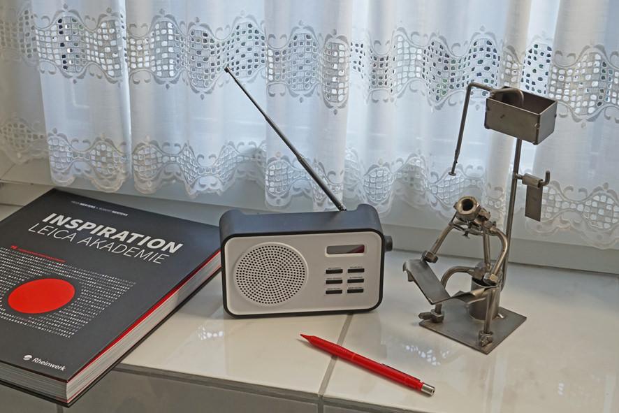 Buch, Radio und Stift auf einer Fensterbank