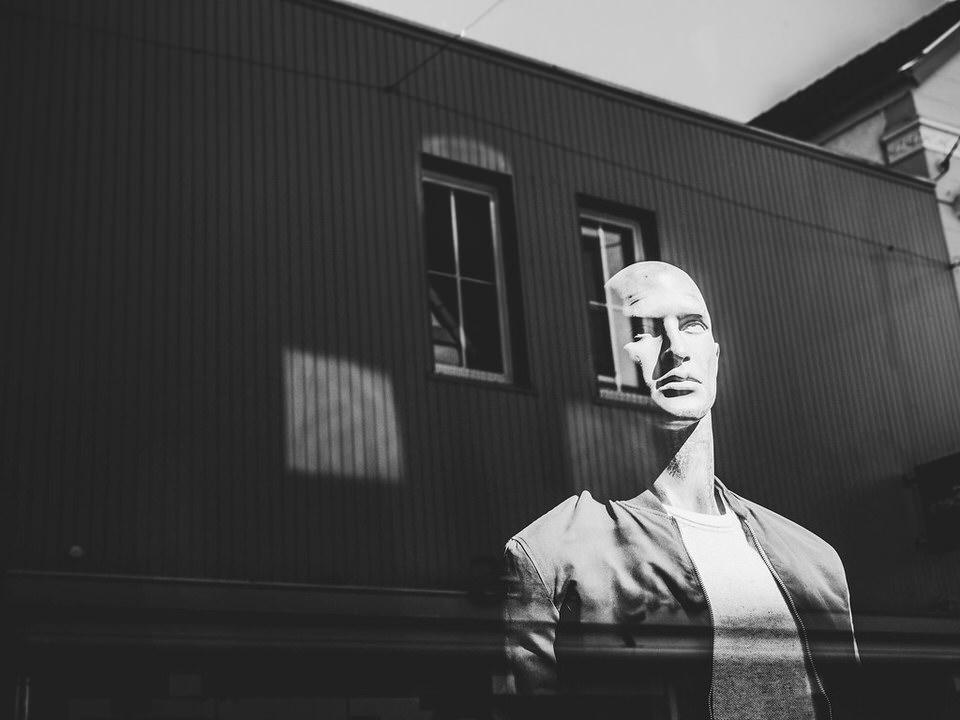 Schaufensterpuppe und Haus als Reflexion durch eine Glasscheibe