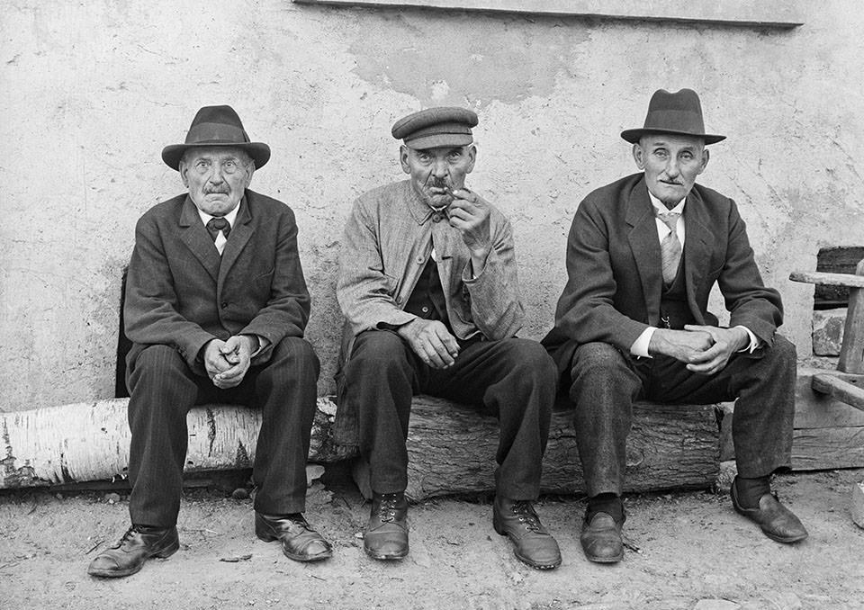 Drei Männer vor dem Haus in guten Anzügen