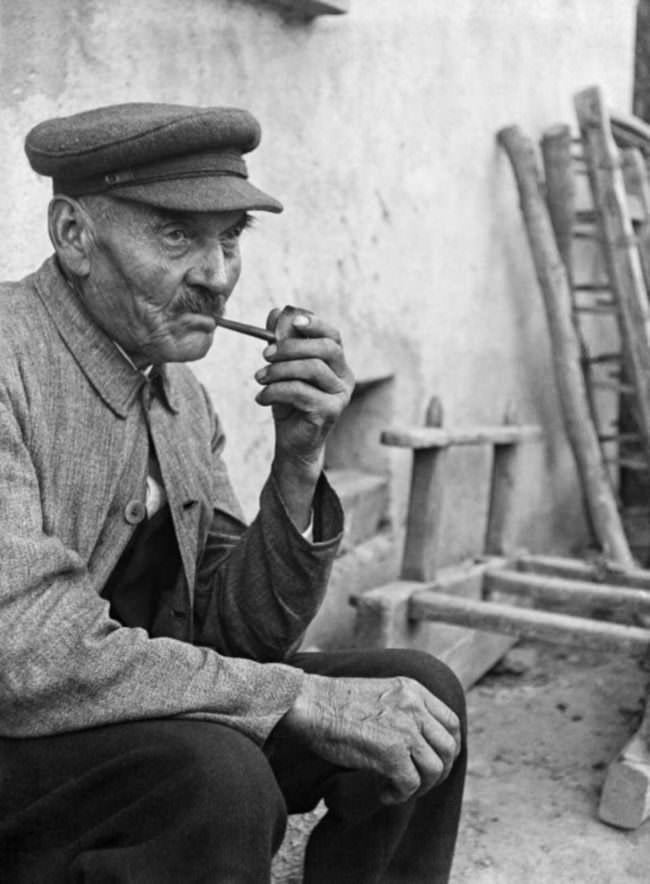 Mann mit Pfeife sitzt vor einem Haus