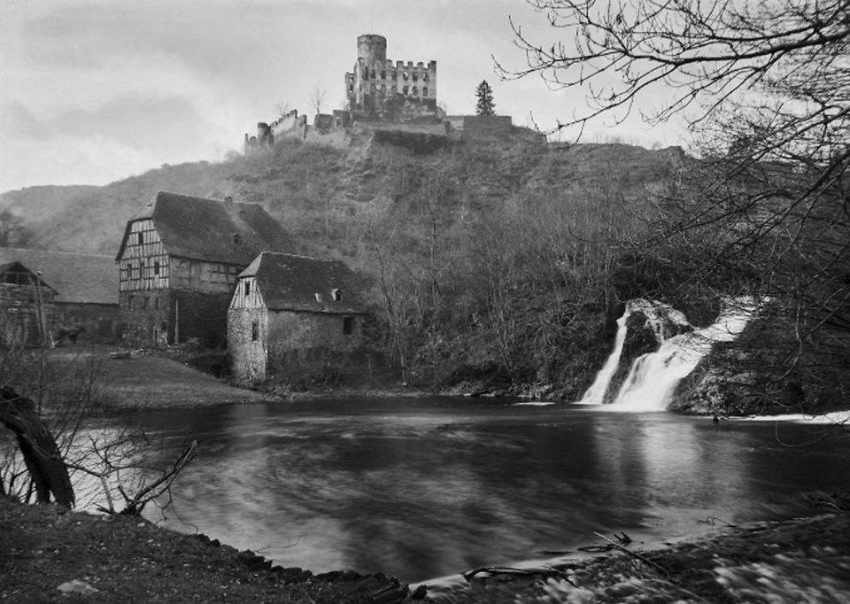 Burg auf einem Berg im Hintergrund davor ein See mit Wasserfall